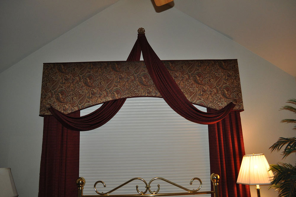 red and gold brocade window valence with artfully draped burgundy curtain