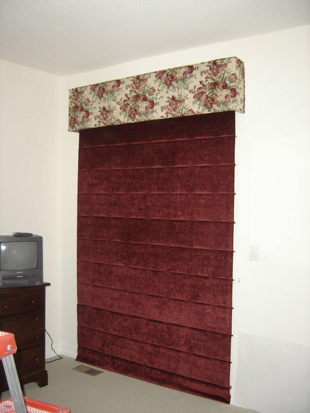 floral window valence and red floor-to-ceiling shade