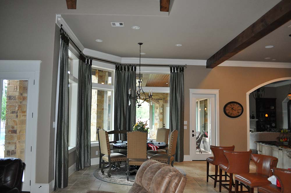 floor-to-ceiling grey curtains hanging in next to small dining table