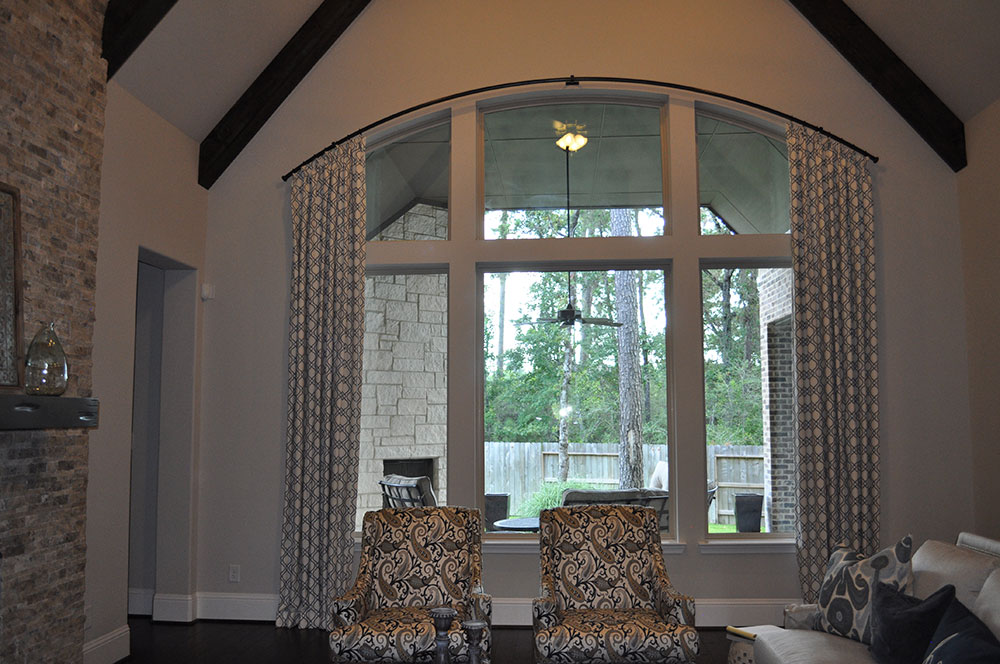 large picture window with arced curtain rod and patterned curtains