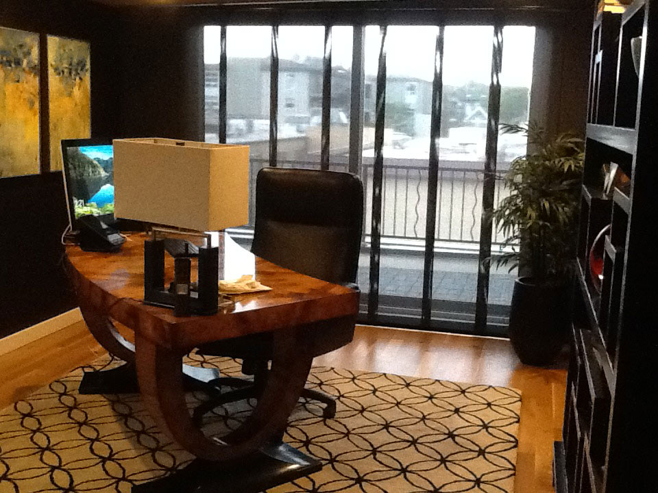 styled office with large desk, window treatments and paintings
