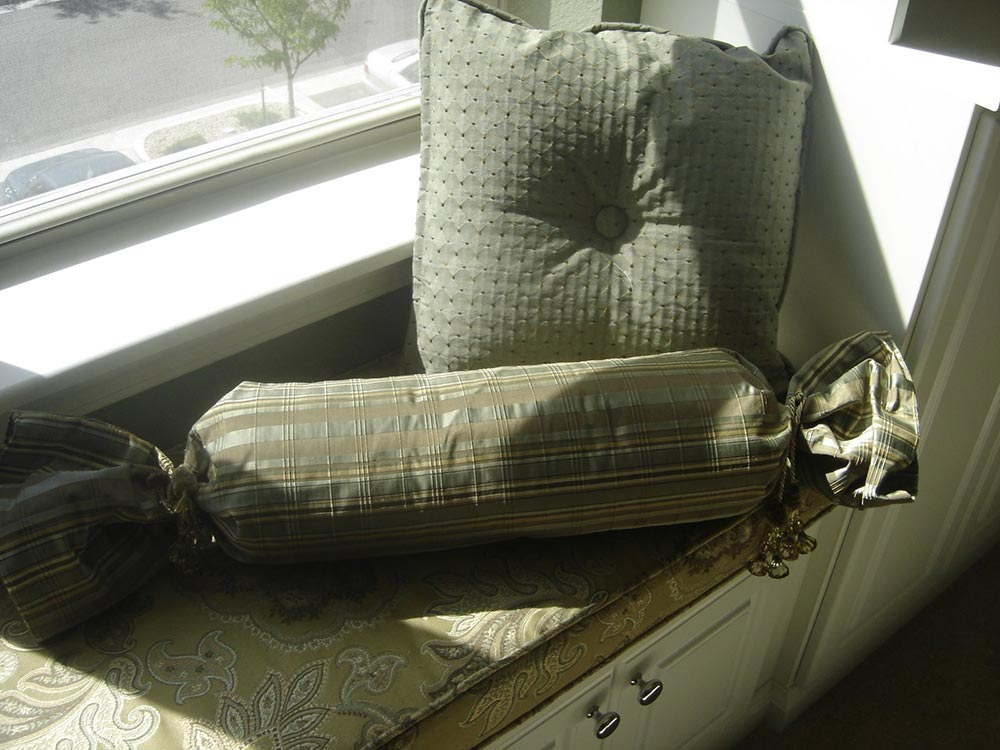 green accent pillows on a window seat