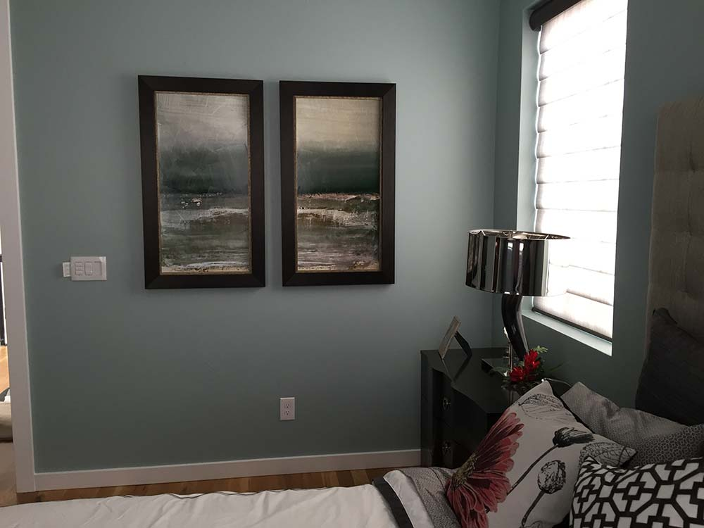 paintings on a wall in bedroom