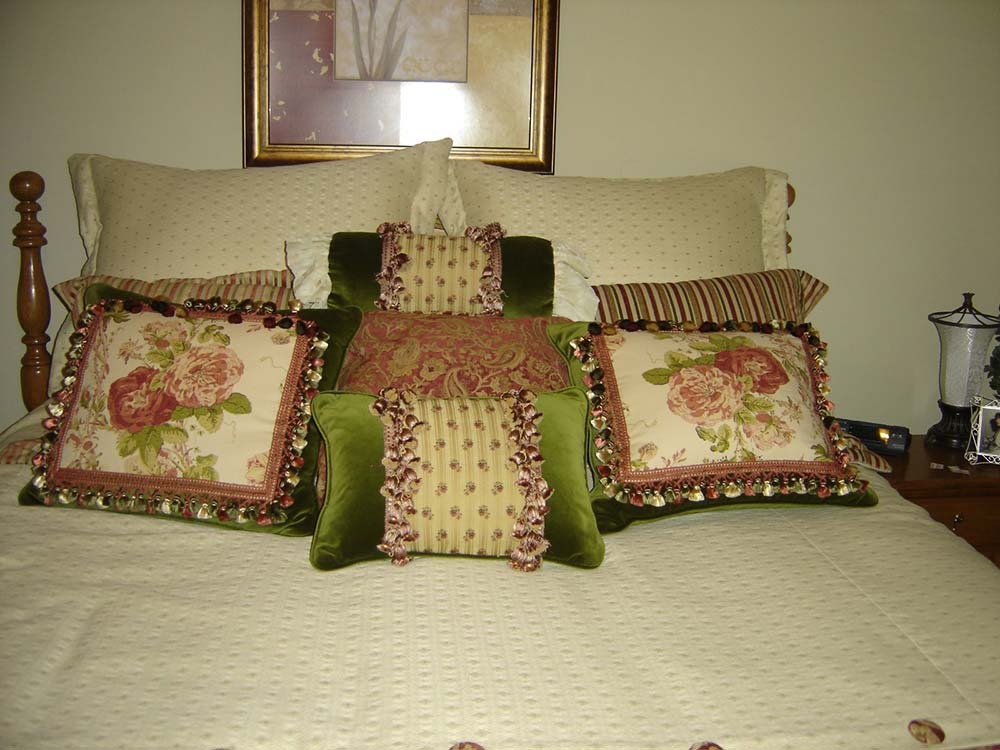 green, pink and beige accent pillows on a light comforter