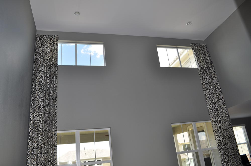 floor-to-ceiling curtains covering two-stories of windows in room with lofted ceilings